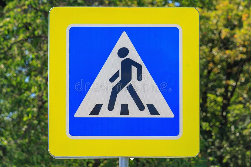 Road sign of Pedestrian crossing against green tree closeup at sunny summer day stock photography