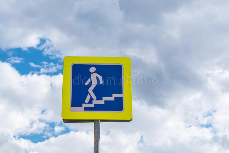 Road sign pedestrian underpass against the blue sky with fluffy clouds. Close-up stock images