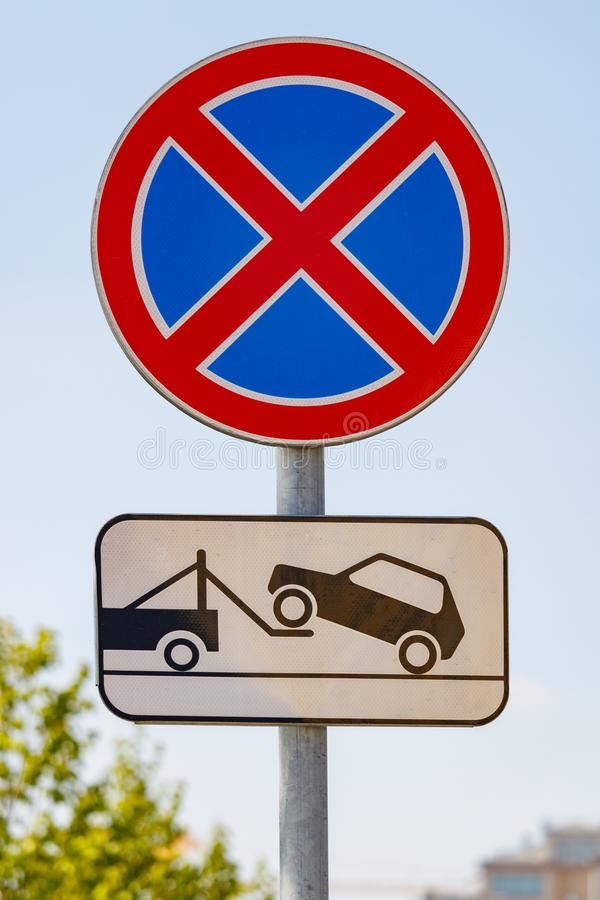 Road sign prohibiting the stopping of the car with a tow truck signboard against blue sky in sunny day closeup stock photo