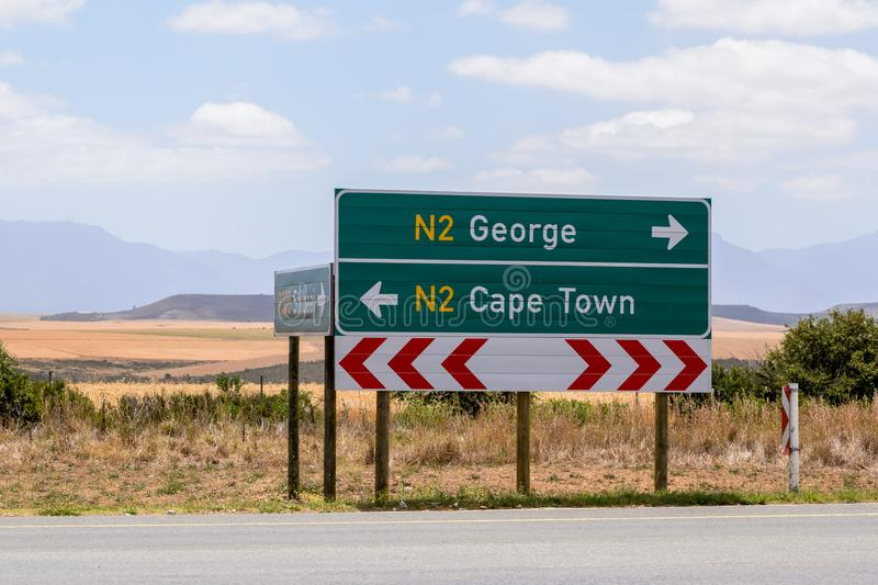 Road sign at the route N2 road in South Africa near Still Bay pointing to Cape Town and George. royalty free stock photos