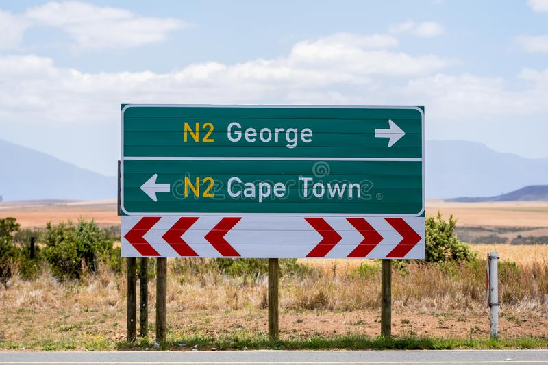 Road sign at the route N2 road in South Africa near Still Bay pointing to Cape Town and George. royalty free stock photography