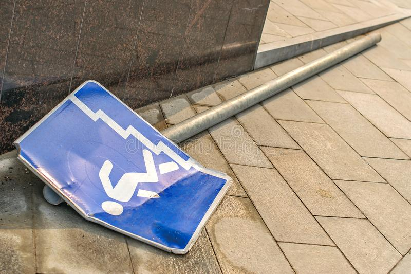 Broken road sign. Road sign signifying an underground passage lying on a tabloid tile stock image