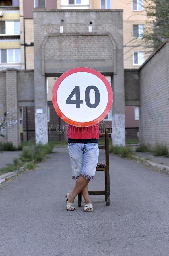 Road sign. Speed ​​limiter, 40 kilometers, legs at the sign, a sign on the road, a round sign, a , travel to the residential area, speed stock photo