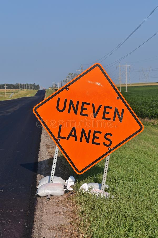 Road sign stating UNEVEN LANES royalty free stock photos