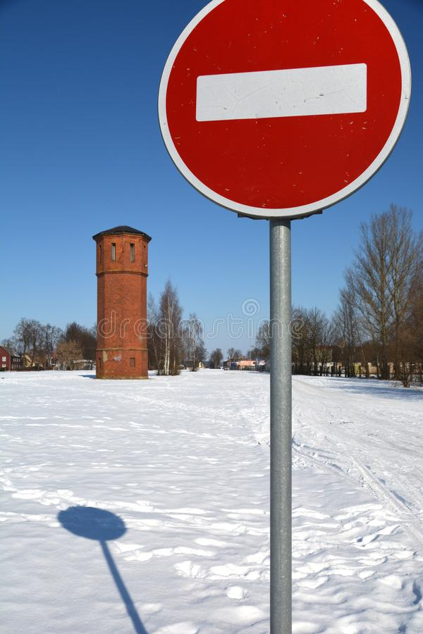 Road sign stop and old red train station tower in winter royalty free stock photos