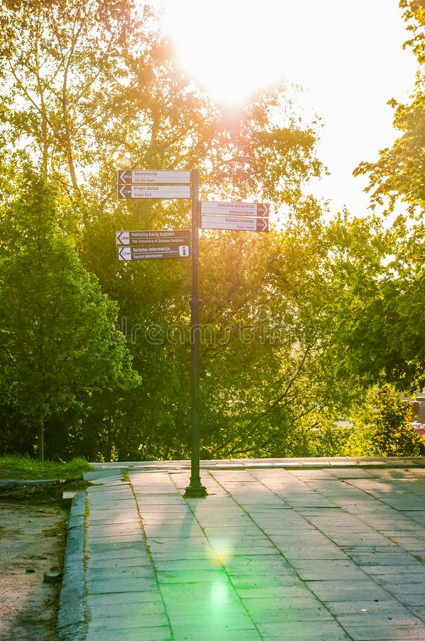 The road sign with sunlight from behind surrounded by plants and trees showing the main attractions and important and popular stock image