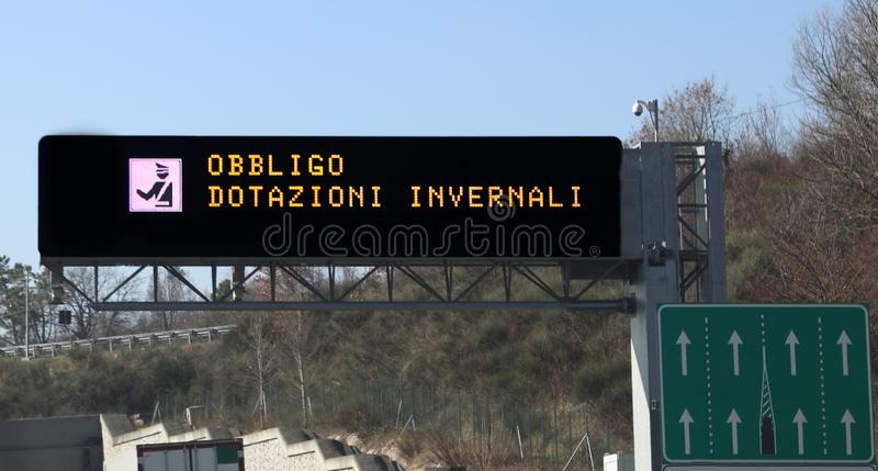 Road sign with text that means winter equipment obligation in It. Warning road sign with text that means winter equipment obligation in Italian Language on the stock image