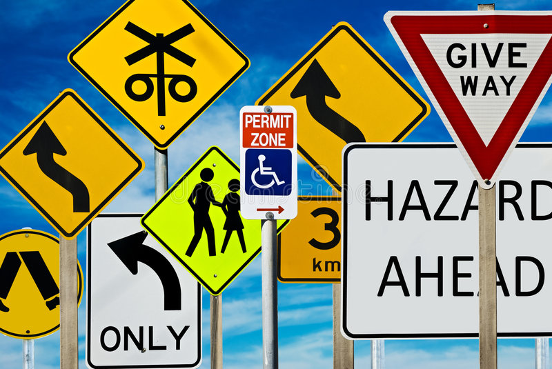 Road Signs. Multiple road signs against a blue cloudy sky. Signs include: giveway, hazard, pedestrian crossing, left turn only, railway crossing and more stock photography