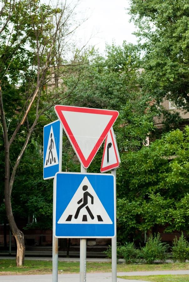 Road signs on a background of trees, give way, pedestrian crossing, traffic rules, road markings. Driving stock photo