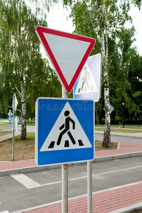 Road signs on a background of trees, give way, pedestrian crossing, traffic rules, road markings stock image