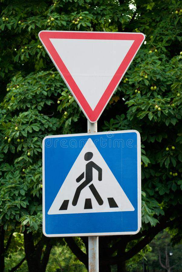 Road signs on a background of trees, give way, pedestrian crossing, traffic rules, road markings. Driving royalty free stock images