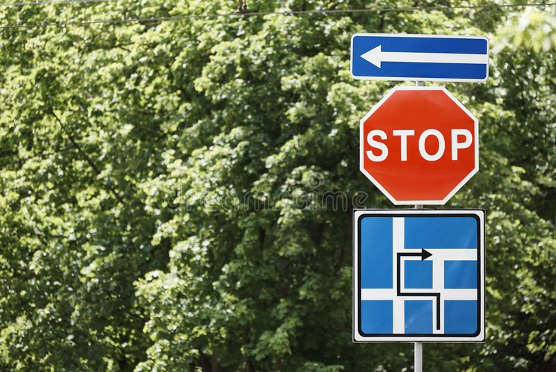 Road signs close-up against. A background of green trees royalty free stock image