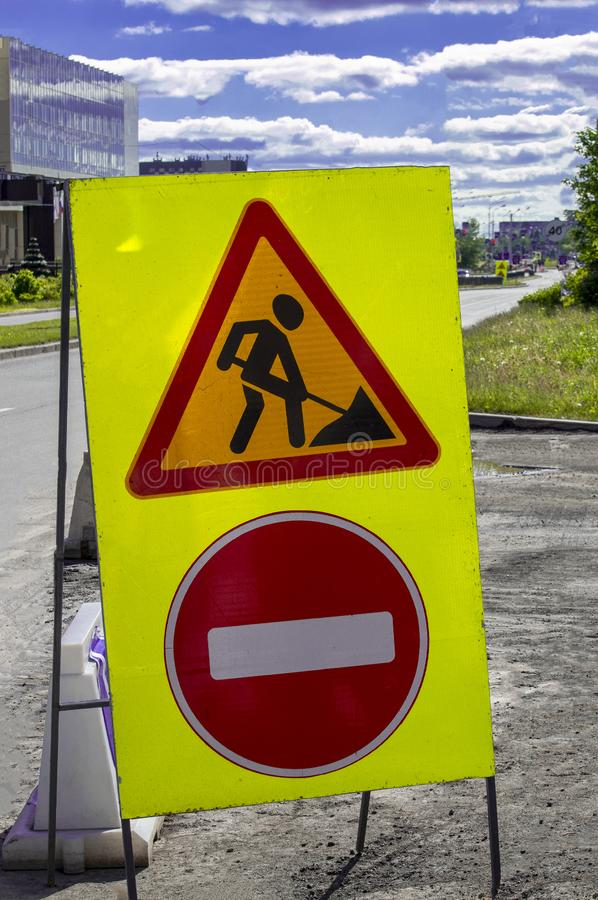 Road signs `Forbidden Access` and `Repair Work` on a city street. royalty free stock image