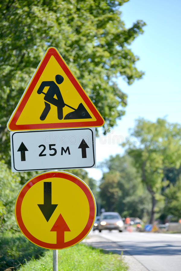 Road signs Roadwork, Advantage before oncoming traffic against a highway.  royalty free stock photo