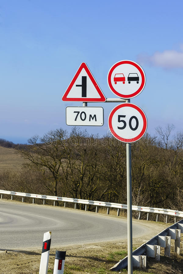 Road signs, speed limits and ban on overtaking at a sharp turn of the highway. The rules of the road stock images