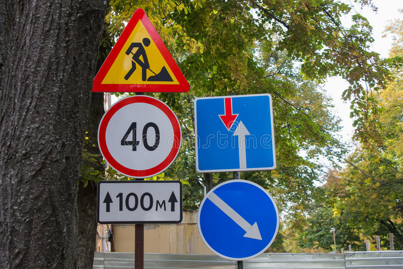 Road signs on the street. Street traffic signs on a background of green foliage stock photography