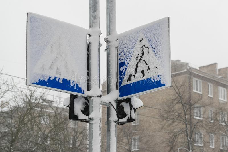 Road signs and traffic lights covered by snow. During heavy snowfall in winter town stock images