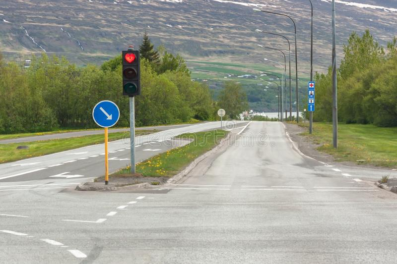 The road with signs and traffic lights on which the red light in the form of a heart stock photography