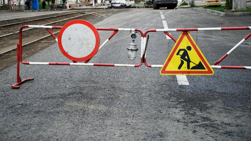 Road signs: traffic is prohibited and construction work is hanging on a temporary fence next to the lantern. Roads and urban stock image