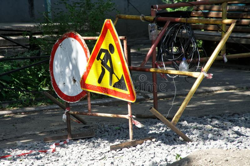 Road signs: traffic is prohibited and construction work installed on a temporary fence in the courtyard of a multi-storey building. Repair and replacement of stock photo