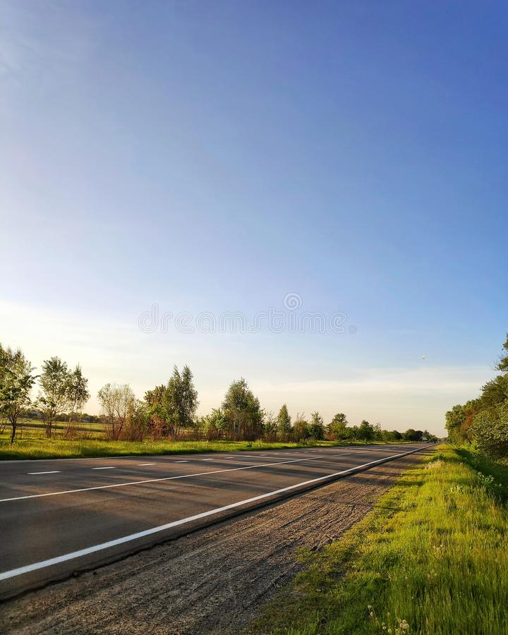 Road in spring and blue clear sky stock images