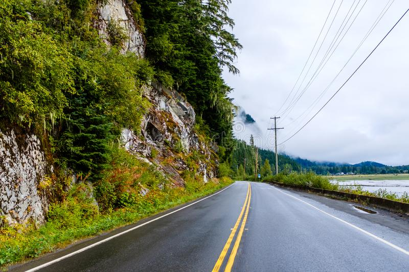 Road by a steep rocky cliff in Canada. Narrow wet road by a steep rocky cliff in Canadian British Columbia royalty free stock photography