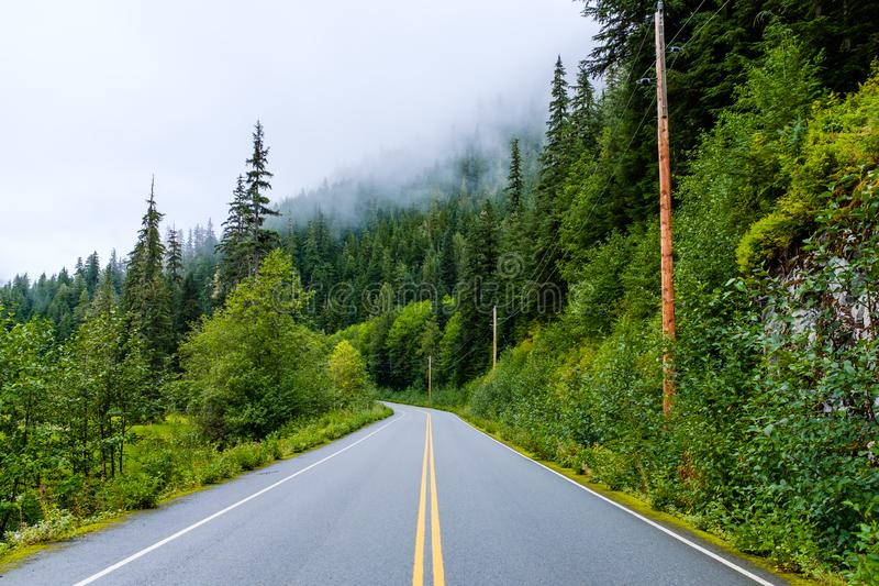 Road by a steep rocky cliff in Canada. Narrow wet road by a steep rocky cliff in Canadian British Columbia stock photography