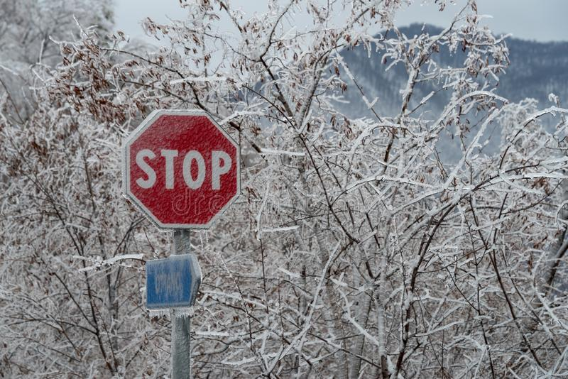 Road stop sign after ice storm. Stop sign covered in ice after the freezing rain stock image