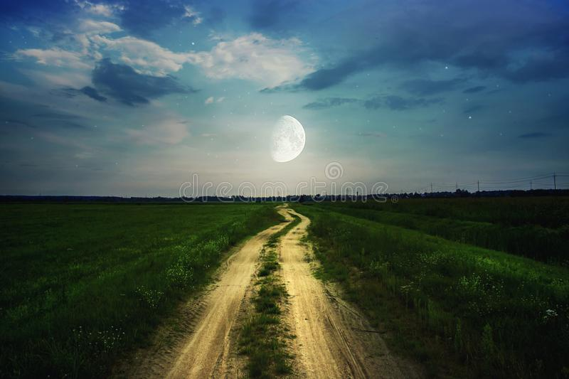 Road stretching into the distance near the green field. Magic blue night sky with moon and stars.  stock photos
