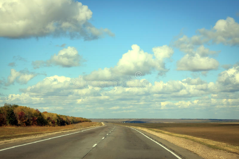 Road in sunny autumn day with cloud on the blue sky. Empty road in sunny autumn day with cloud on the blue sky stock image