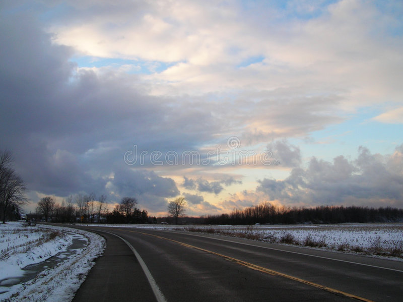 Road at Sunset. A road in winter with high contrast clouds at sunset royalty free stock photo