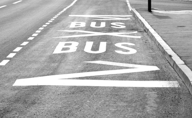 Road surface markings at bus stop on empty city street stock images