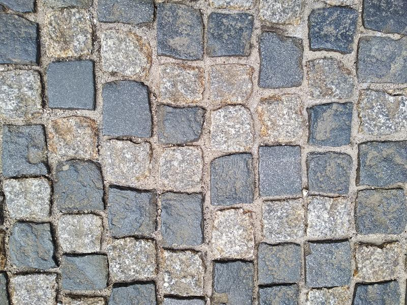 The road surface of the stones - paving stones. the road, made for many years, reliable road surface in old cities. age-old royalty free stock image