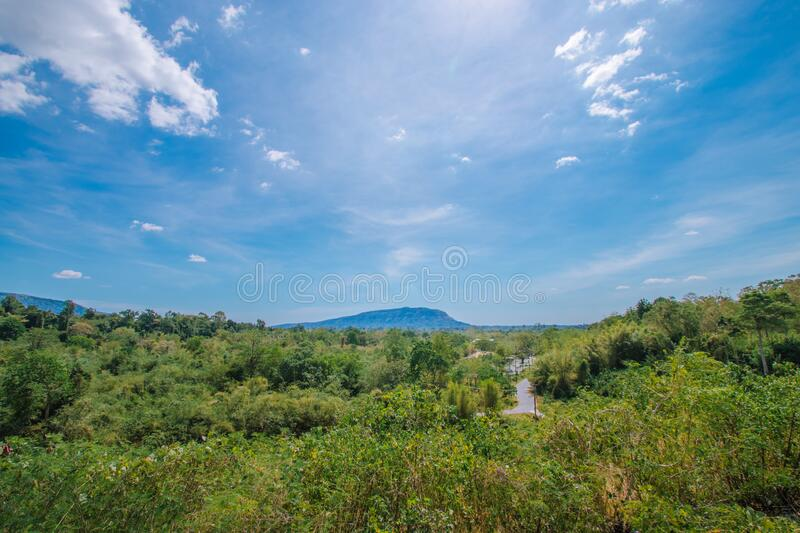 A road surrounded by green trees with mountains behind under the blue sky. In thailand stock photography