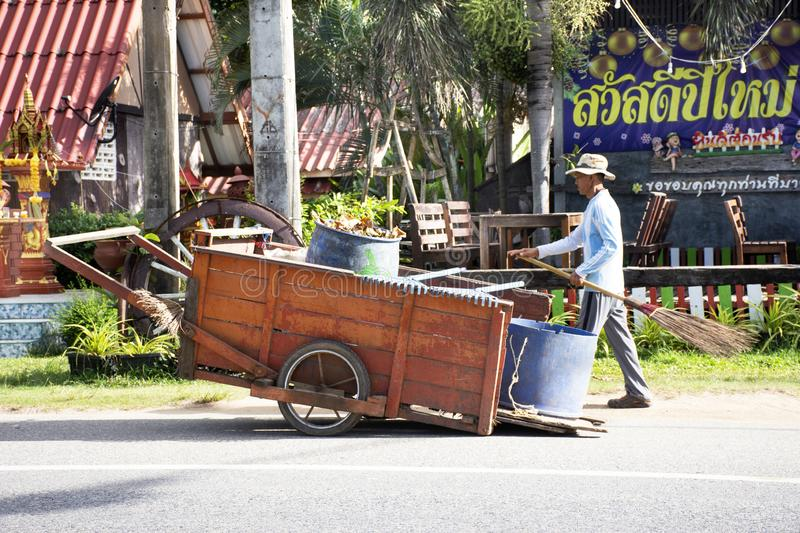 Road sweeper thai people worker cleaning and keeping junk garbage with cart on street at Ban Phe road in Rayong, Thailand royalty free stock image