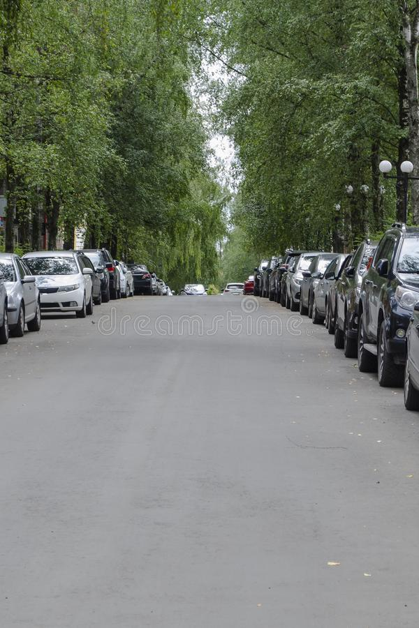 Cars are parked on the street very tightly to each other. A road with tightly parked cars on both sides royalty free stock photo