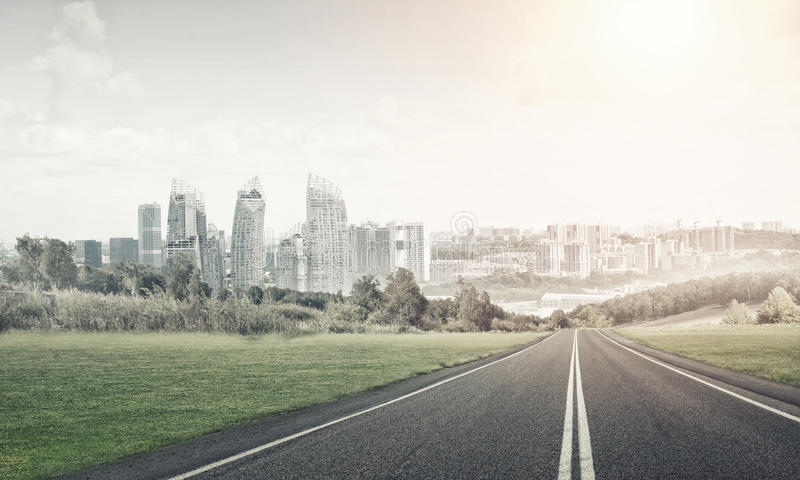 Road to big city. Natural landscape with asphalt road and modern city royalty free stock photo