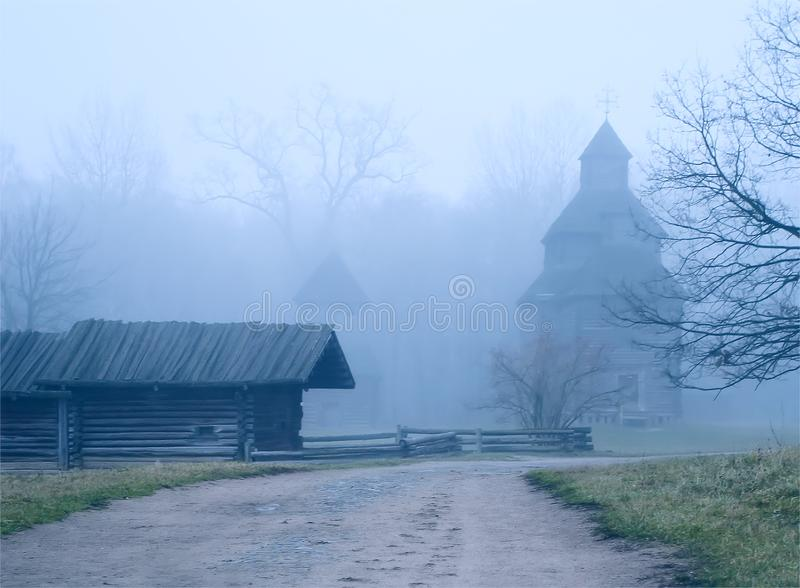 The road to the church and the old house in the fog royalty free stock photo
