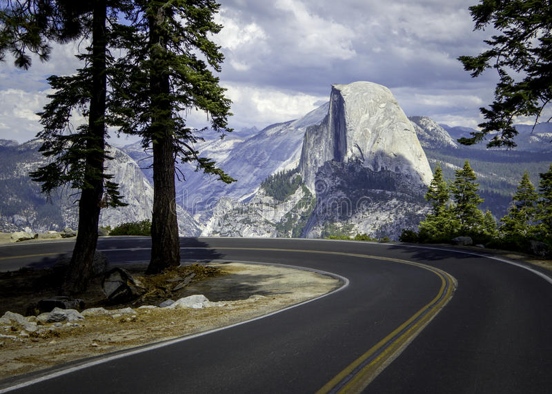 On the road to El Capitan. A beautiful stunning landscape picture of a winding road in the Yosemite mountains with El Capitan mountain in the background royalty free stock photography
