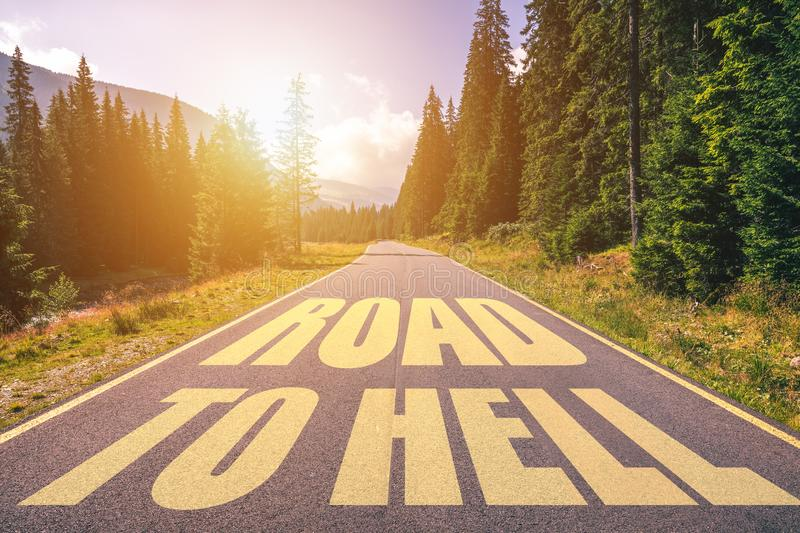 Road to hell written on the street in the mountains. Road to hell text on the highway stock image