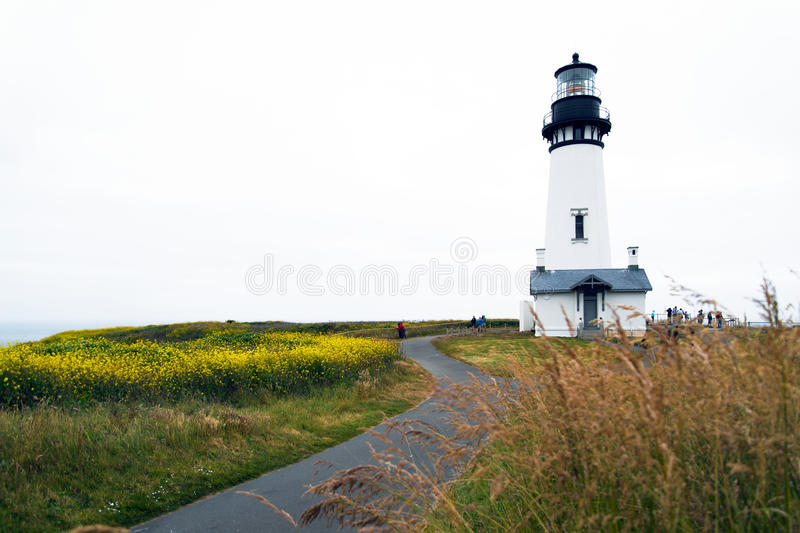 Road to high round lighthouse standing on promontory Pacific coa stock photos