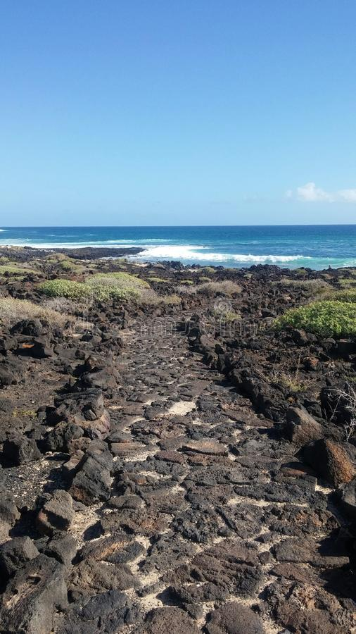 Road to infinity. The path of volcanic stones that goes towards the infinite ocean Lanzarote, Spain royalty free stock images