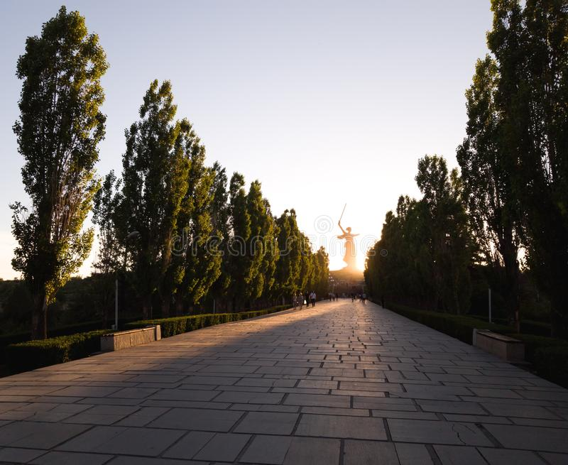 The road to Mamayev Kurgan in Volgograd in the sunset and the silhouette of the monument Motherland calls in the distance royalty free stock image