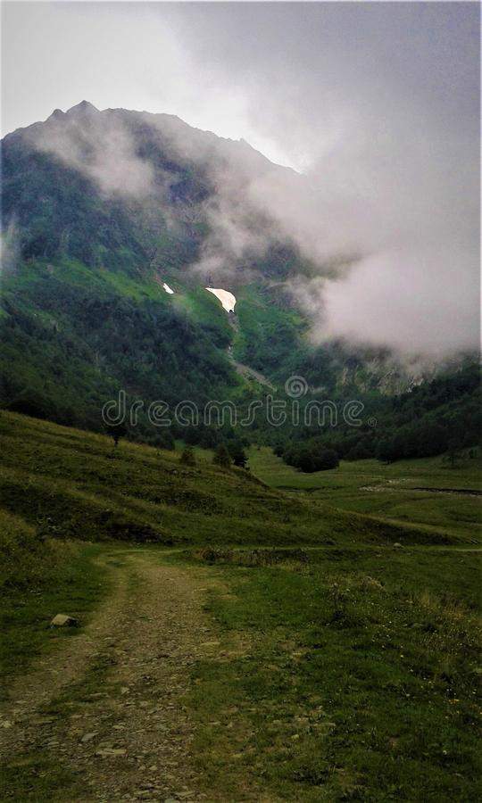 Road to a mountain with clouds royalty free stock images