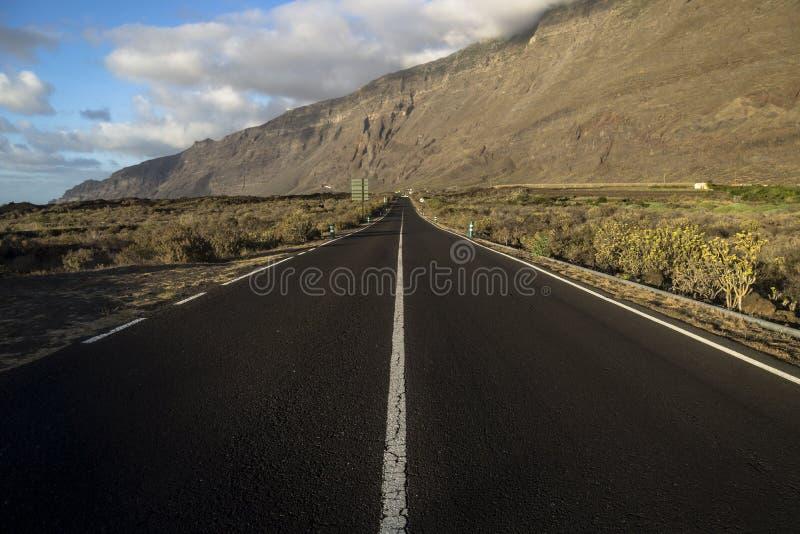 Road to the mountain wall. Endless road in el golfo valley, el hierro stock photos