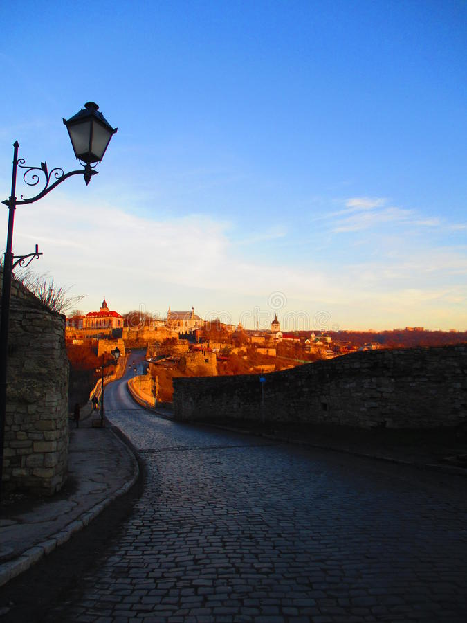 Road to the old town, Kamenets Podolskiy, Ukraine. View of road over turkish bridge and the old town in the beams of the setting down sun stock photo