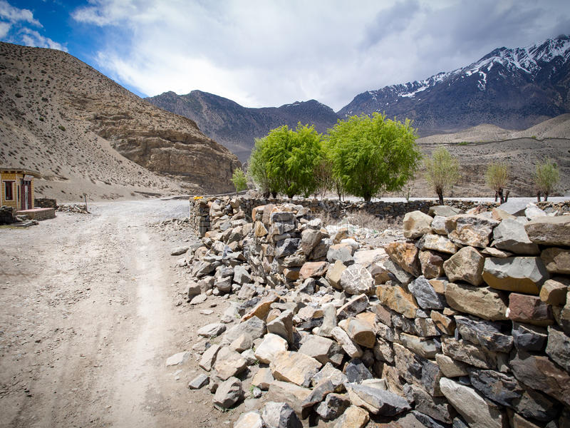 Road to the overcast weather snowy mountain at distance along with the stone wall and few trees. Jomsom, Annapurna Conservation Area, Nepal stock photos