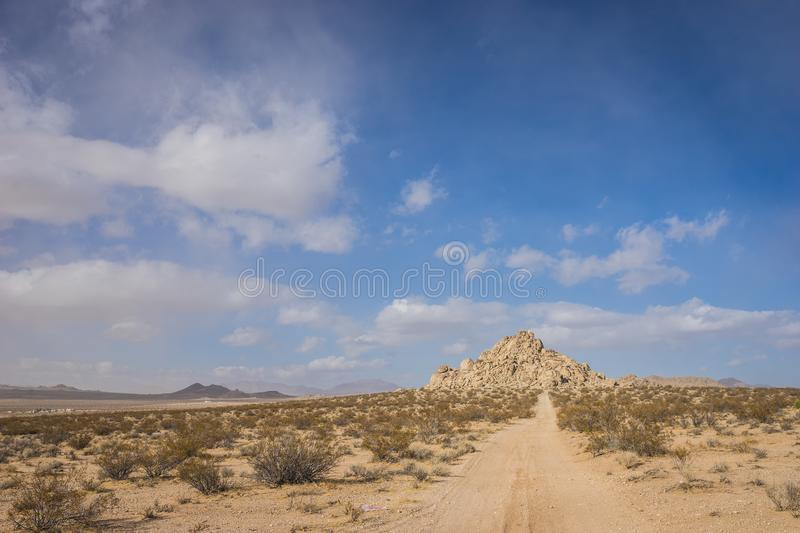 Road to Pile of Rocks. Long sandy dirt road leads down to a hill made of rock boulders stock image