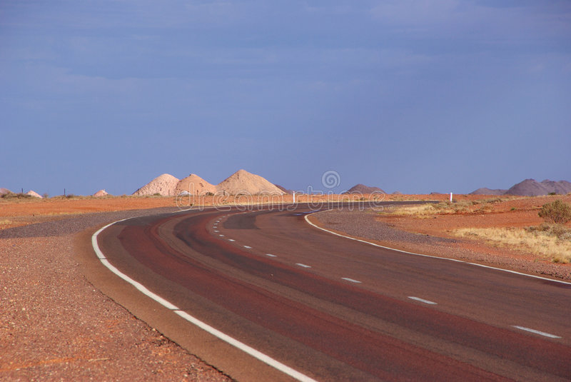 Road to Riches. Piles of rock and dust dug from opal mines line the road to Coober Pedy in South Australia's outback. Coober Pedy, South Australia stock photo