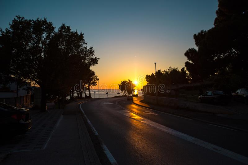 The road to the sea against the sunset sky stock photography
